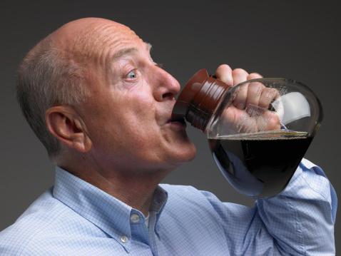 Senior man drinking coffee from pot